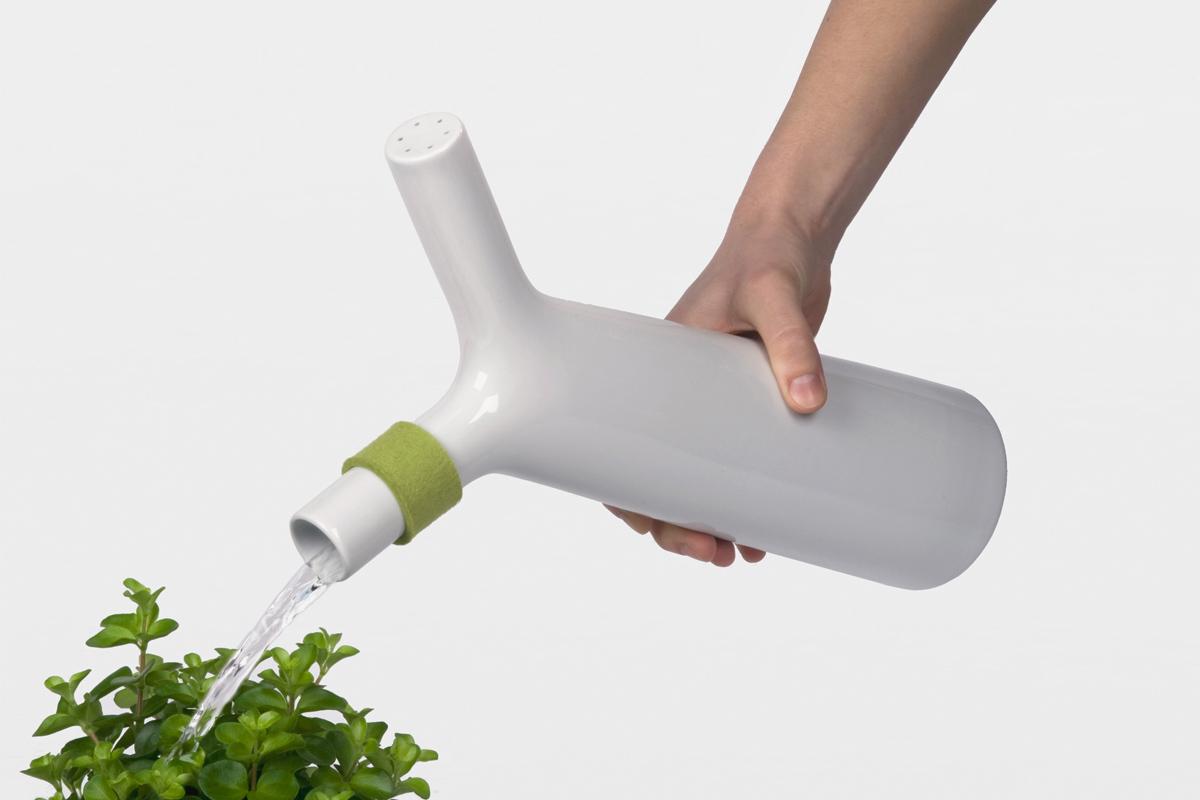watering green flowers from a porcelain watering bottle