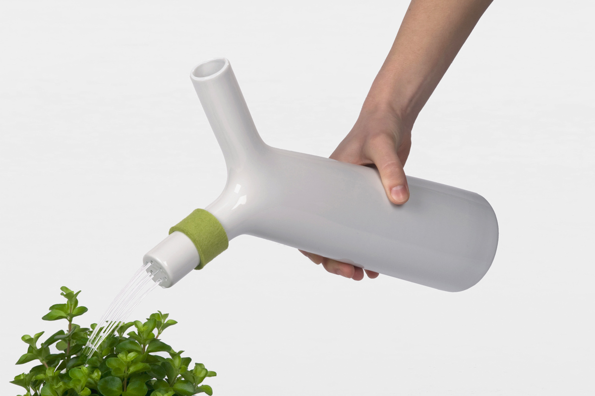 showering green herbs with a porcelain watering can
