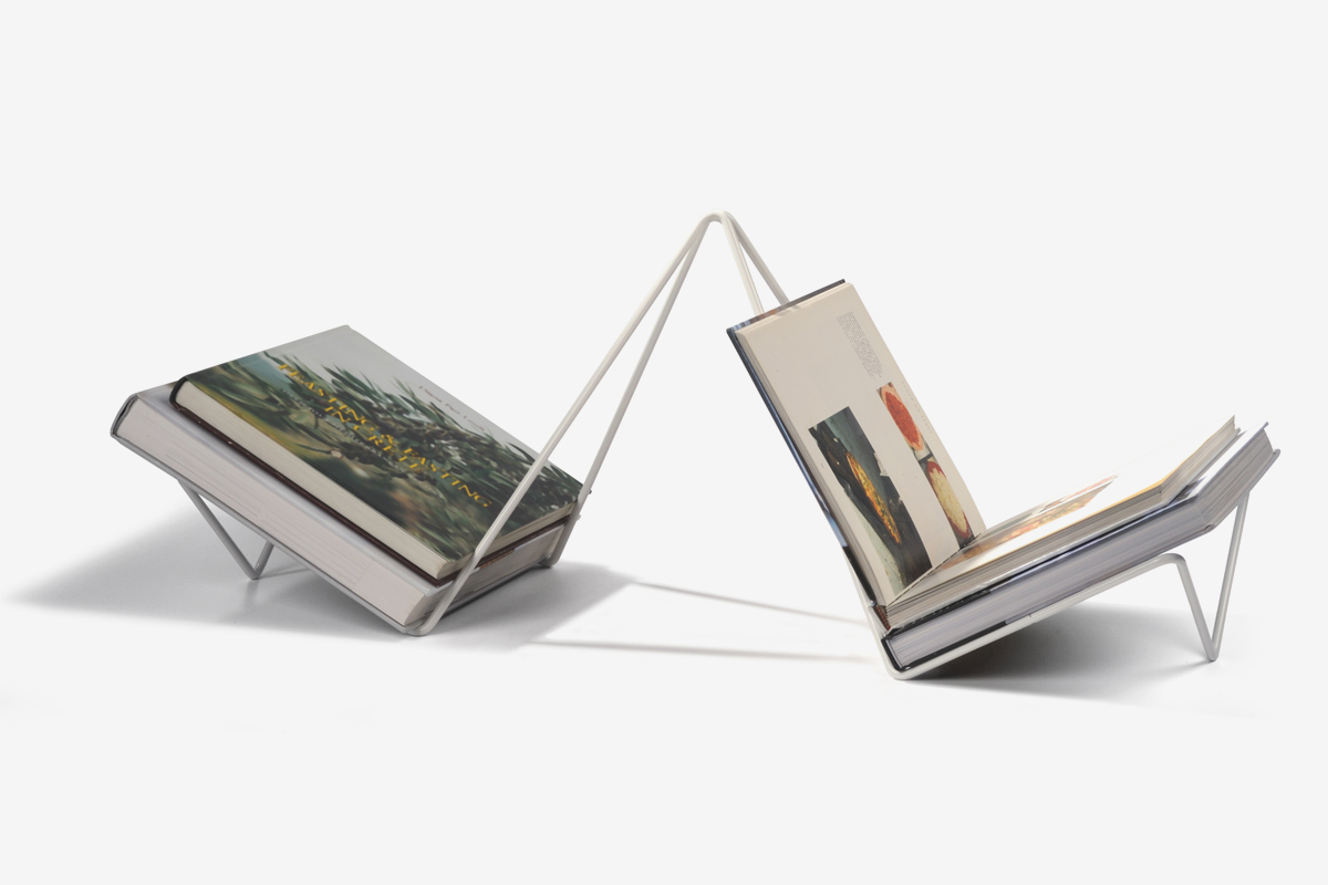 magazine rack in white bent steel rod with an open and closed books