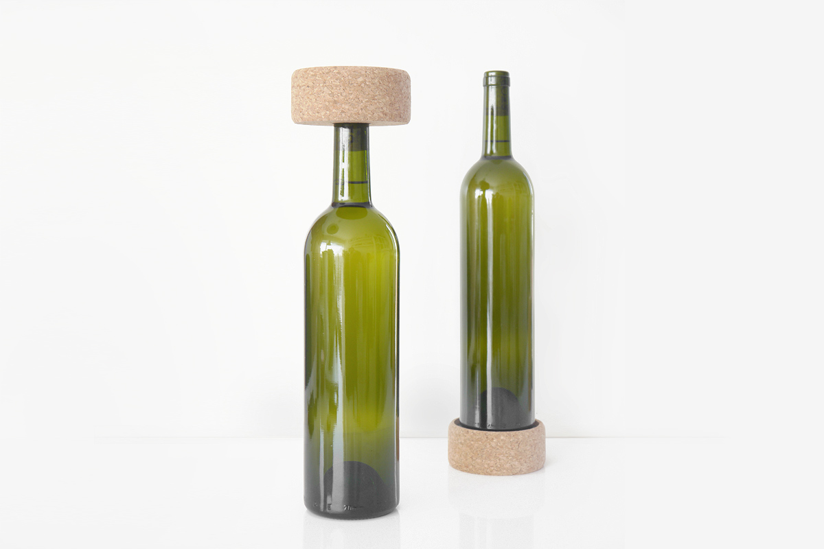 Two green wine bottles with a cork stopper and cork bottle coaster